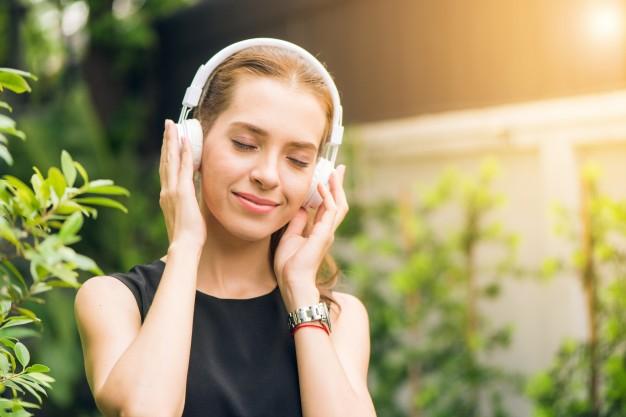 conceito-de-lazer-e-tecnologia-de-pessoas-jovem-atraente-que-escuta-musica-no-leitor-de-musica-ao-ar-livre-menina-do-hipster-que-gosta-das-musicas-em-seus-fones-de-ouvido-no-parque-da-manha-lens-flare_1253-970